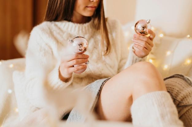 Женщина расслабляется дома и держит декоративные елочные шары