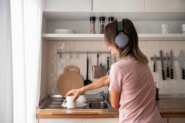 Женщина расслабляется дома во время прослушивания музыки