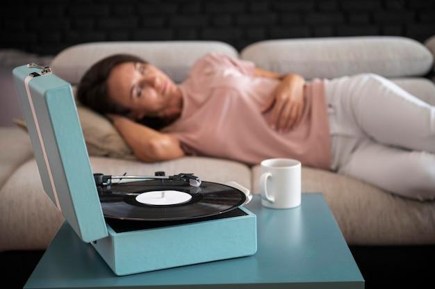 Женщина расслабляется дома во время прослушивания виниловой музыки