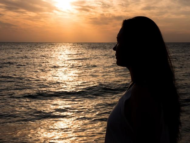 美しい夕日の間にビーチでリラックスした女性。休暇の人間のリラクゼーション