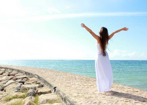 彼女の自由を楽しんでいる腕を開いてビーチでリラックスした女性