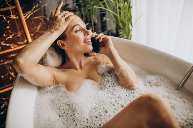 Donna che si distende in bagno con bolle e parla al telefono