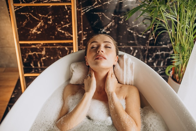 Donna che si distende nella vasca da bagno con le bolle