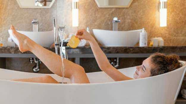 Donna che si distende nella vasca da bagno durante il bagno