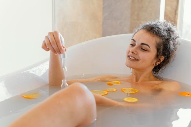 Donna che si distende nella vasca da bagno con fette d'arancia