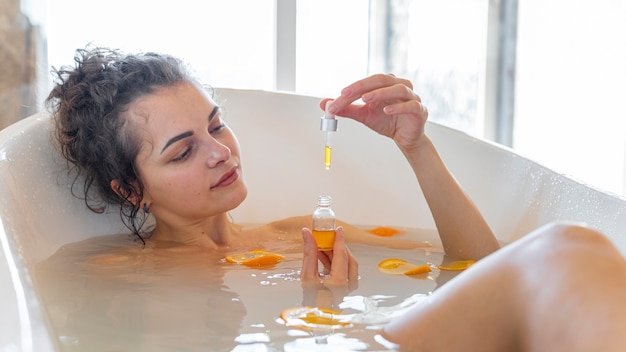 Woman relaxing in bathtub with orange slices