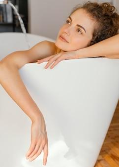 Donna che si distende nella vasca da bagno