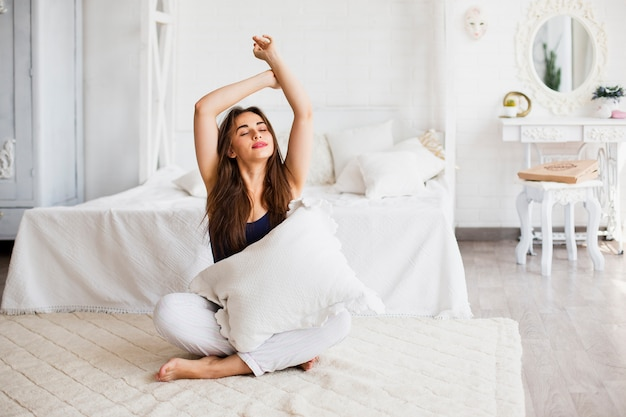 Woman relaxing in bed and holding pillow