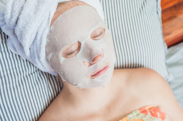 Woman relaxing in bed with a facial mask