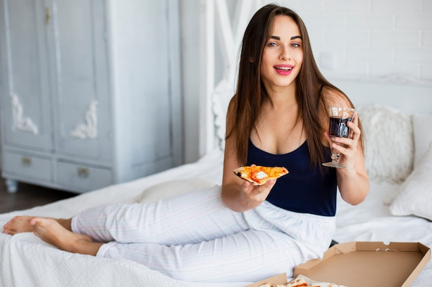 Woman relaxing in bed with wine and pizza