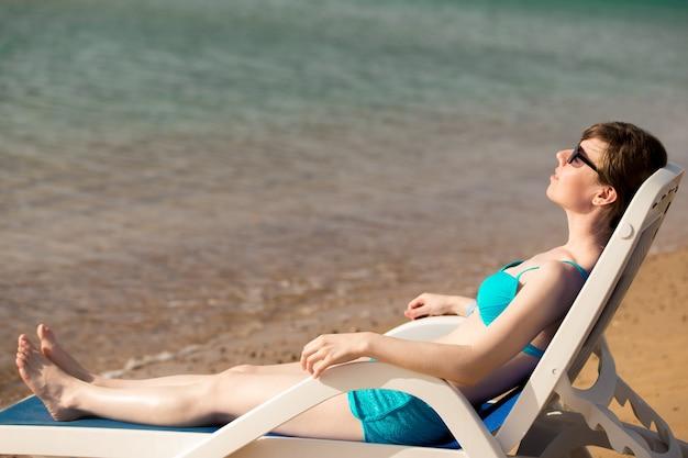 Woman relaxing on blue deckchair