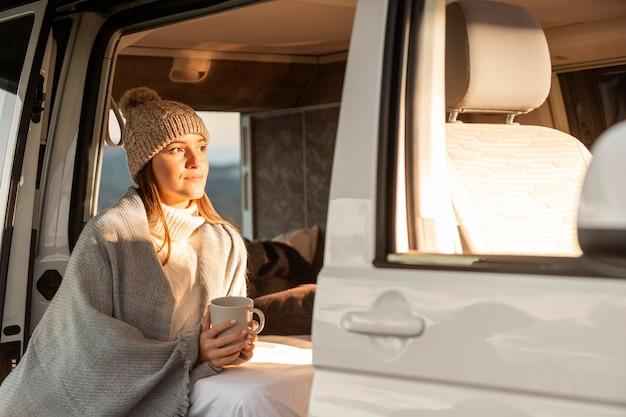 Donna che si rilassa accanto in macchina durante un viaggio e tenendo la tazza