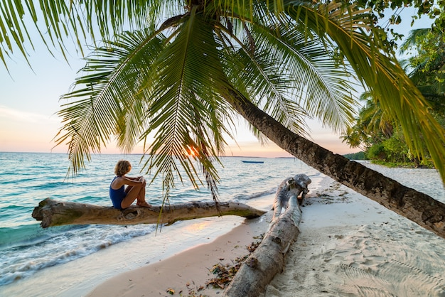Woman relaxing under coconut palm frond on scenic white sand beach, sunny day, turquoise transparent water, real people. indonesia, kei islands, moluccas maluku, wab beach