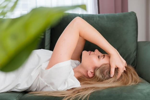 Donna che si distende sulla vista frontale del divano