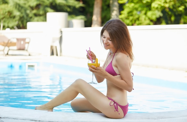 Woman relaxing and drink a cocktail at swimming pool