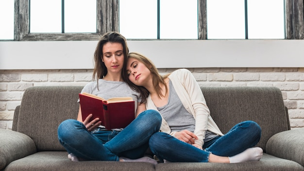 Woman relaxing on her girlfriend's shoulder sitting on sofa reading the book