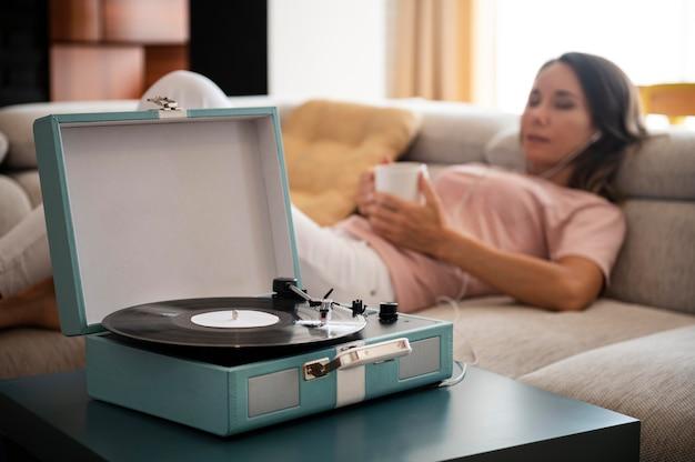 Donna che si rilassa a casa mentre ascolta musica in vinile