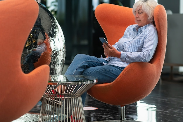 銀色の球体に映るカラフルな浴槽の椅子でくつろぐ女性