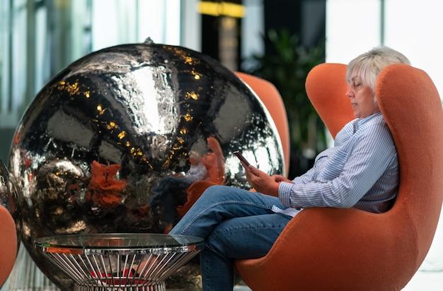 オレンジ色の快適な椅子で携帯を持ってリラックスする女性