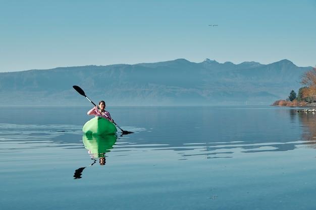 평온한 호수 한가운데 카약에서 편안한 여자.