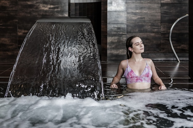 Женщина расслабляется в пузырящемся бассейне со струей воды