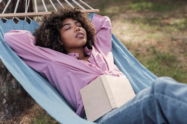 本で野外キャンプしながらハンモックでリラックスする女性
