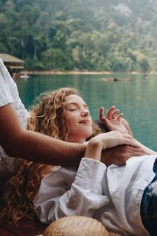 彼女のボーイフレンドの膝の上でリラックスできる女性