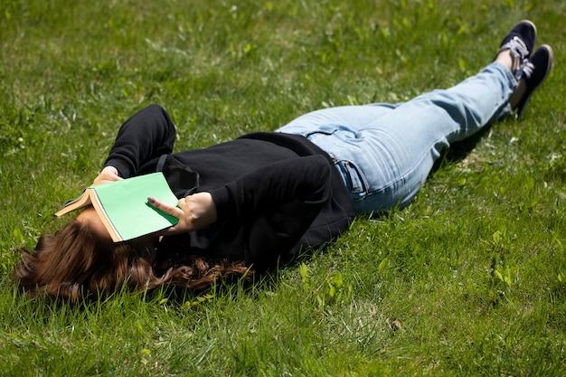 顔に開いた紙の本と公園の緑の芝生の上に横たわって自然の中でリラックスした女性