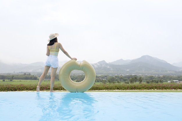 Woman relaxing in infinity swimming pool looking at mountain view
