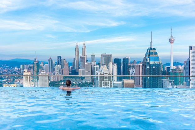 Woman relaxing in infinity swimming pool roof top looking at beautiful city skyscraper view kuala lumpur, malaysia