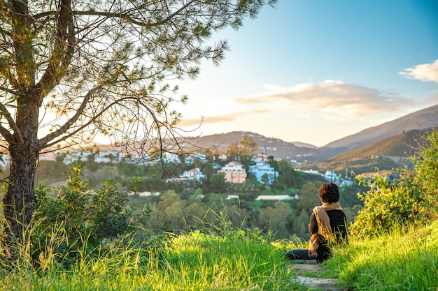 Woman relaxing and meditating at sunset on green hill with beautiful view of countryside and mountains