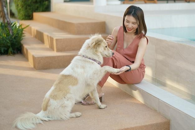 かわいい犬とスイミングプールのそばでリラックスした女性。