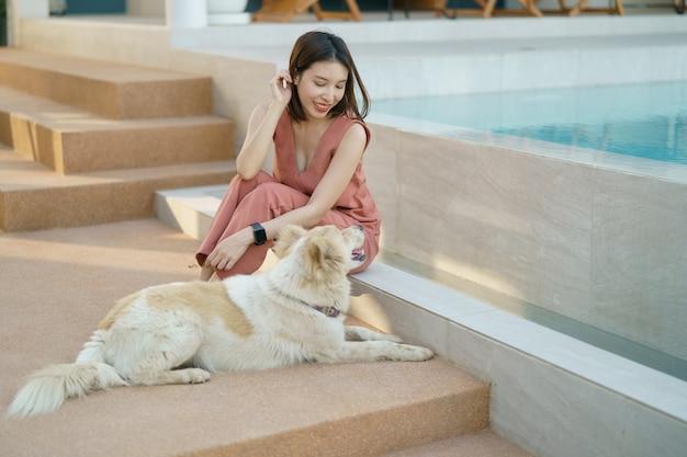 Женщина расслабляющий возле бассейна с милой собакой.