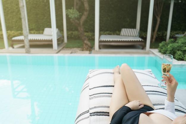 Женщина расслабляется у бассейна и пьет шампанское.