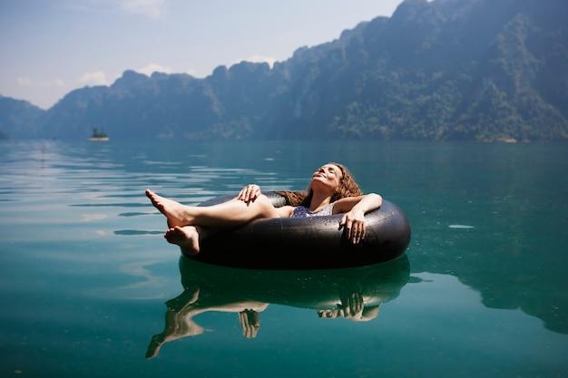 Женщина расслабляется на плавающем кольце