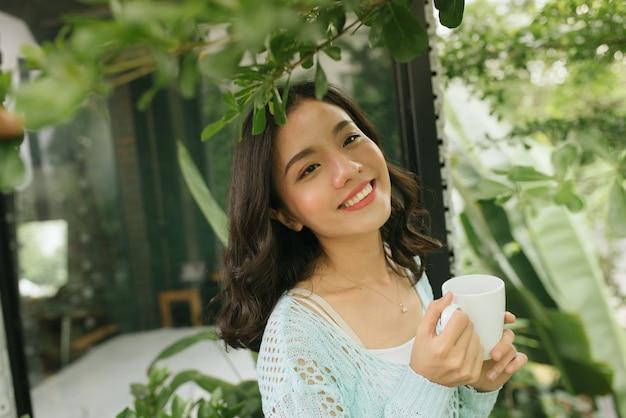 커피 또는 차 한 잔을 들고 발코니에서 휴식을 취하는 여성