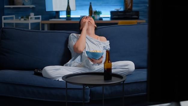 Женщина расслабляется на диване, ест попкорн, смеясь, смотря смешной фильм