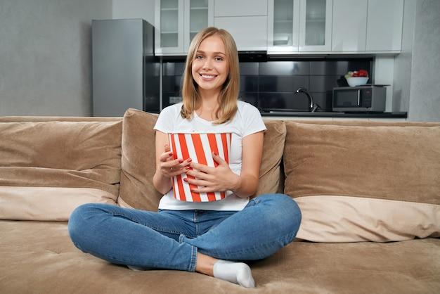 Женщина расслабляется на диване с попкорном и смотрит телевизор