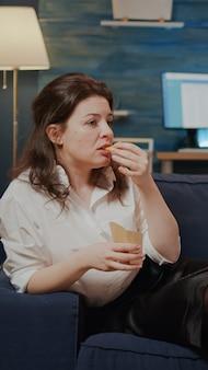 自宅で持ち帰り用の食べ物とソファでリラックスする女性