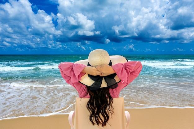 ビーチでデッキチェアでリラックスし、海を見ている女性。