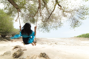 Woman relaxing on wooden swing under tree on tropical beach