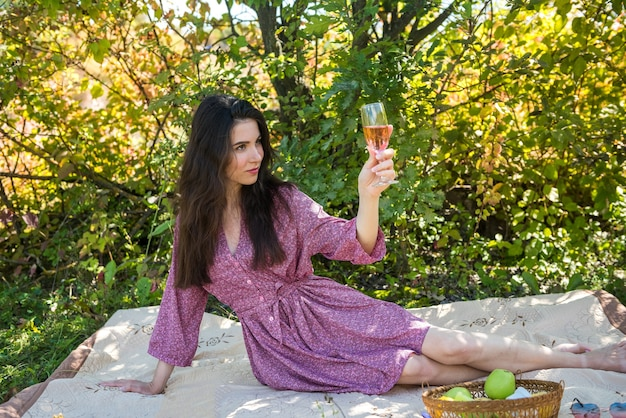 Woman relaxing outdoors  taking a layer of wine, summer time