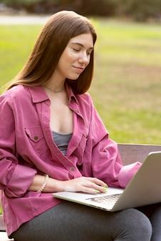 Donna che si distende all'aperto rimanendo sul suo computer portatile