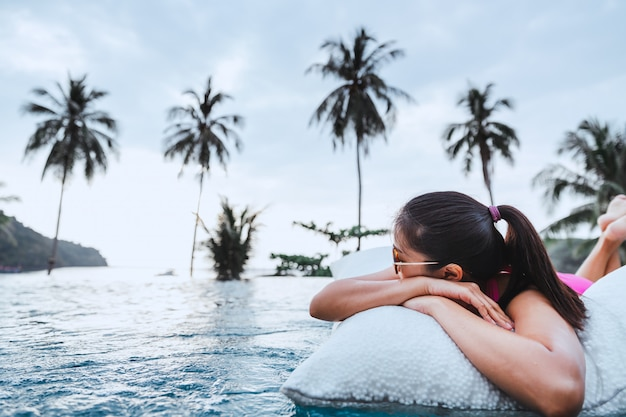 Woman relaxing in pool at a resort