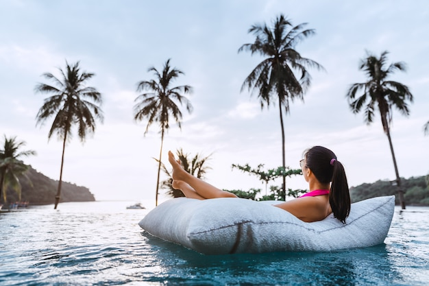 Woman relaxing in pool at sunset