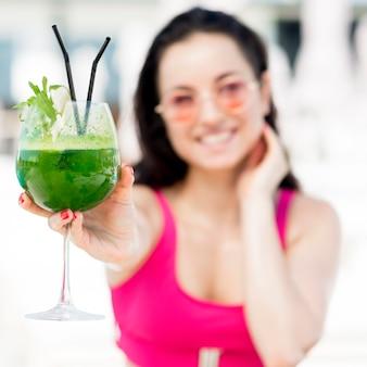 Donna che si rilassa allo stagno con un drink Foto Gratuite