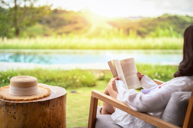 秋の公園で本を読んでリラックスする女性