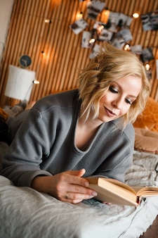 Woman relaxing and reading book on cozy bed - wooden wall and photos with lights - blurred background - vertical photo