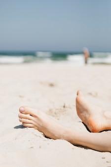 Donna che si distende nella sabbia su una spiaggia
