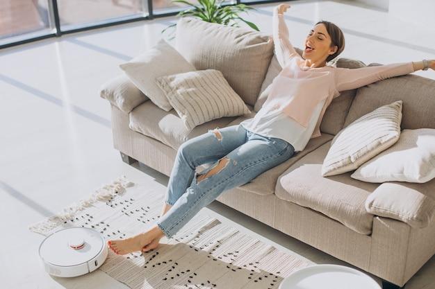 Donna che si rilassa sul divano mentre il robot aspirapolvere fa i lavori domestici